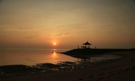 Sunrise at the gazebo Bali, Indonesia. People enjoying the early morning breeze at the gazebo. Low tide. Serene water shot Royalty Free Stock Photos
