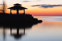 Sunrise and Gazebo. Glow of sunrise is the backdrop for the silhouette of a gazebo with its reflection off of a smooth lake. Long exposure royalty free stock photography