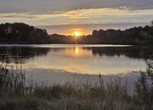 Sunrise over a quiet forest lake stock images