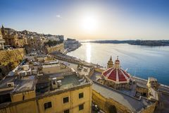 Sunrise at the Grand Harbour of Malta with the ancient walls of Valletta Stock Image