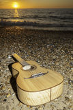 Sunrise guitar - after the vacation party!. A classical parlour sized acoustic guitar laying on the shore at sunrise or sunset. The image is symbolic of vacation Stock Photography