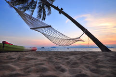 Sunrise with hammock and coconut palm trees on tropical beach background Stock Photography