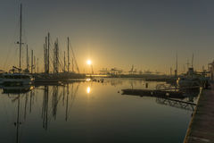 Sunrise in the harbor of Valencia, the sun rises between docked sailboats and cargo port cranes Stock Photos