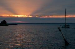 Sunrise in the harbour. A catamaran runs against the rising sun stock image