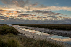Sunrise haven. Sunrise at Saltfleet haven in Lincolnshire where creek heads out to sea with reflections Royalty Free Stock Image
