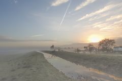 Sunrise in Holland on a misty winter morning with rime on the green grass stock image