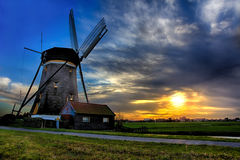 Sunrise House and the Giant of Netherlands. Sunrise over a beautiful little house guarded by the giant windmill of Netherlands Royalty Free Stock Image
