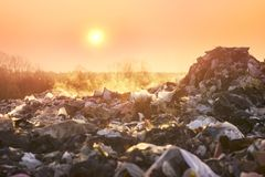 Poisonous fumes on the landfill. Sunrise on a huge trash can after a fire. Smoke and steam, poisonous gases and fumes escape from the waste of the city in the royalty free stock images