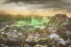 Poisonous fumes on the landfill. Sunrise on a huge trash can after a fire. Smoke and steam, poisonous gases and fumes escape from the waste of the city in the royalty free stock image