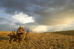 Sunrise hunter and dogs in moody arid landscape Stock Images