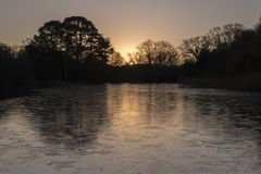 Sunrise on an icy morning at the Ornamental Pond, Southampton Common stock photo