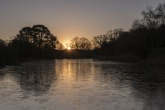 Sunrise on an icy morning at the Ornamental Pond, Southampton Common royalty free stock photo