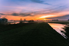 Sunrise ignites the sky at the river bank Stock Photography
