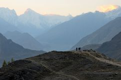Sunrise among the Karakoram mountains in Hunza Valley Pakistan. Hunza Valley, Gilgit-Baltistan province, Pakistan - September 30, 2016: Men gathered on top of a Royalty Free Stock Image