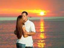 Sunrise kiss. Young couple kissing near the sea at sunrise royalty free stock photo