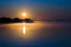 Sunrise on the lake. With steam. The sun is reflected in the water. There are trees on the horizon Royalty Free Stock Image