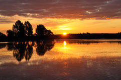 Sunrise on a lake. On a quiet morning Stock Photography