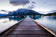 Sunrise on a lake in Banff National Park Alberta Canada. Boats and houses reflection on the lake viewed from the dock stock photo