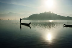 Sunrise on lake,fisherman rowing the boat Stock Images