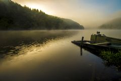 Old looking small boat on an lake at sunrise time with fog. Sunrise at the lake on a foggy day. There is two old boats half sunk on the right. Light passing Royalty Free Stock Images