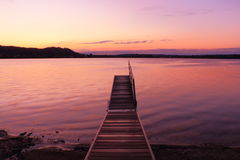 Sunrise by a lake inspiring relax and quietness. View of a pier on lake at sunrise in the warm tones of pink inspiring relax and quietness Stock Photos