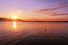 Sunrise by a lake inspiring relax and quietness. View of a pier on lake at sunrise in the warm tones of pink inspiring relax and quietness Royalty Free Stock Images