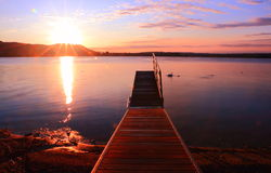 Sunrise by a lake inspiring relax and quietness. View of a pier on lake at sunrise in the warm tones of pink inspiring relax and quietness Stock Photo