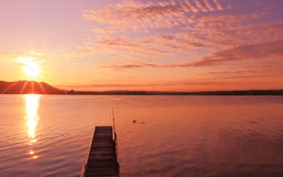 Sunrise by a lake inspiring relax and quietness. View of a pier on lake at sunrise in the warm tones of pink inspiring relax and quietness Royalty Free Stock Photo