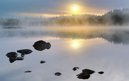 Sunrise. On a lake with rocks in the foreground Stock Images