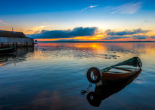 Sunrise on Lake Seliger with an old boat in the foreground. Stock Photos