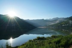 Sunrise by Lake in Summer. The sun is rising over the hill by the lake r. It`s very beautiful and quiet. It`s a good place to camping,hiking,fishing and Royalty Free Stock Image