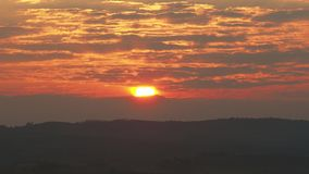 Sunrise in the lands of Tuscany. The sun rises between strips of clouds. Spring time stock video footage