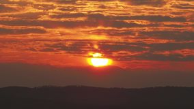 Sunrise in the lands of Tuscany. The sun rises between strips of clouds. Spring time stock footage