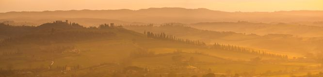 Sunrise in the lands of Tuscany. Warm colors on the hills and haze. Spring time royalty free stock image