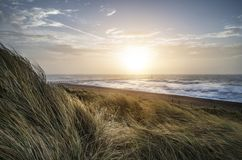 Beautiful sunrise landscape image of sand dunes system over beac Royalty Free Stock Photography