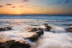 Sunrise landscape of ocean with waves clouds and rocks royalty free stock photography