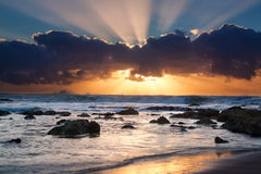 Sunrise landscape of ocean with waves clouds and rocks. On beach Royalty Free Stock Photos