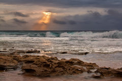 Sunrise landscape of ocean with waves clouds and rocks Royalty Free Stock Image