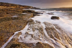Sunrise landscape of ocean with waves clouds and rocks Stock Images