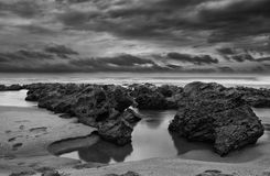 Sunrise landscape of ocean. With waves clouds and rocks black and white Royalty Free Stock Photos
