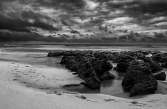 Sunrise landscape of ocean. With waves clouds and rocks black and white Stock Image