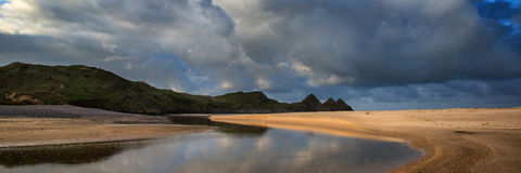 Sunrise landscape panorama Three Cliffs Bay in Wales with dramatic sky stock image