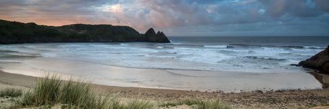 Sunrise landscape panorama Three Cliffs Bay in Wales with dramat Stock Photography