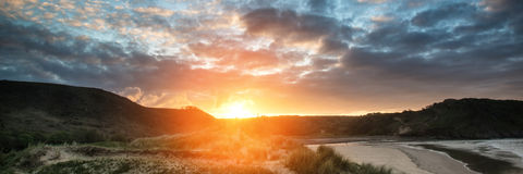 Sunrise landscape panorama Three Cliffs Bay in Wales with dramatic sky royalty free stock photo
