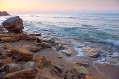 Sunrise landscape,  the rocky sea coast and water waves Stock Photo