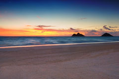 Sunrise at Lanikai Beach,. Colorful skies just before sunrise, with footprints in foreground on sand, at Lanikai Beach, in Kailua, Hawaii Royalty Free Stock Images