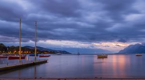 Sunrise on Leman lake and boats. Fantastic orange color at sunrise on the lake Leman and part of Ouchi port at the windy morning. City of Lausanne, canton Vaud Stock Images