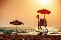 Sunrise with life guard station silhouette Royalty Free Stock Photos