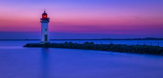 Sunrise on a lighthouse. Beautiful colors of sunrise on a sea lighthouse in the morning with a blue sea Stock Images
