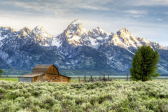 Sunrise lights the water and the land in The Grand Tetons. Royalty Free Stock Images